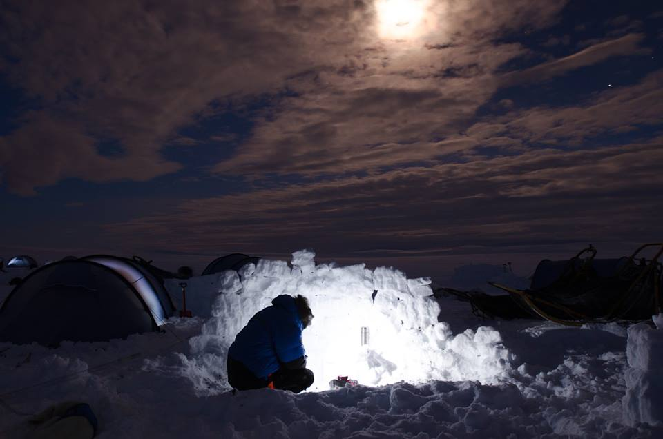 It's close to midnight by the time most Fjällräven Polar participants have an opportunity to boil water for dinner. To shelter us from Råstu's nasty wind, we construct walls out of blocks of snow. (Photo by Søren Hauris Larsen. All rights reserved.)