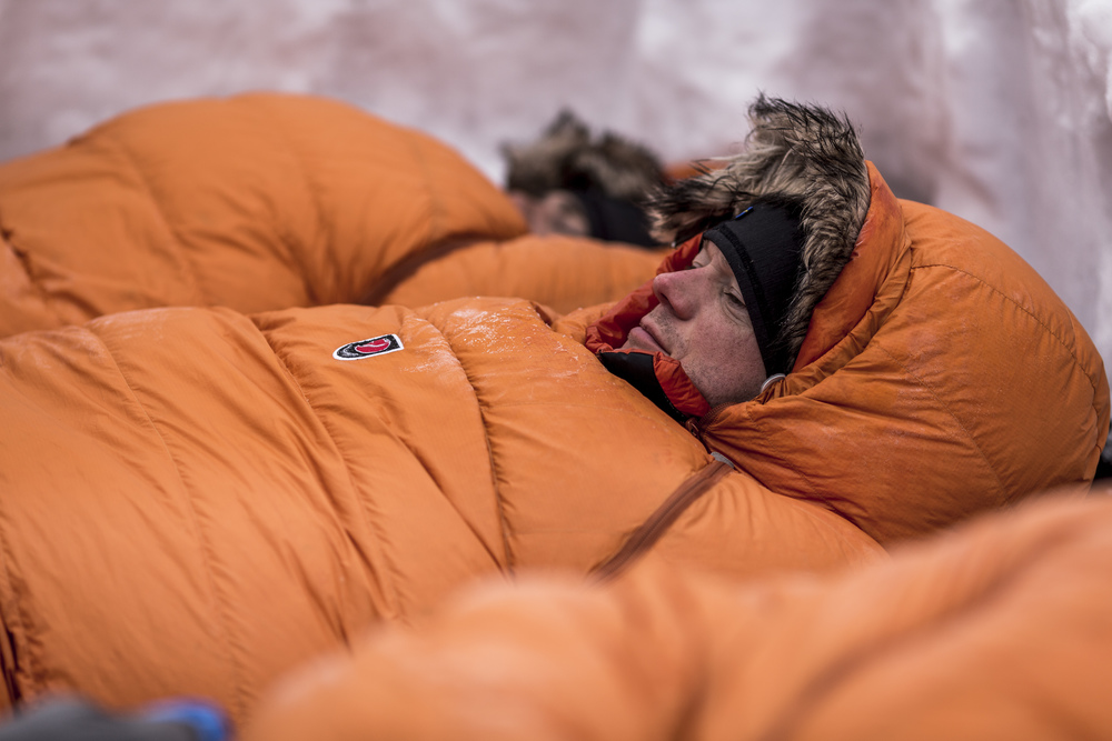 UK participant Phil Raisbeck awakens in his snow shelter in Sevvovouma, on the final morning of Fjällräven Polar. (Photo by Håkan Wike for Fjällräven International. All rights reserved.)