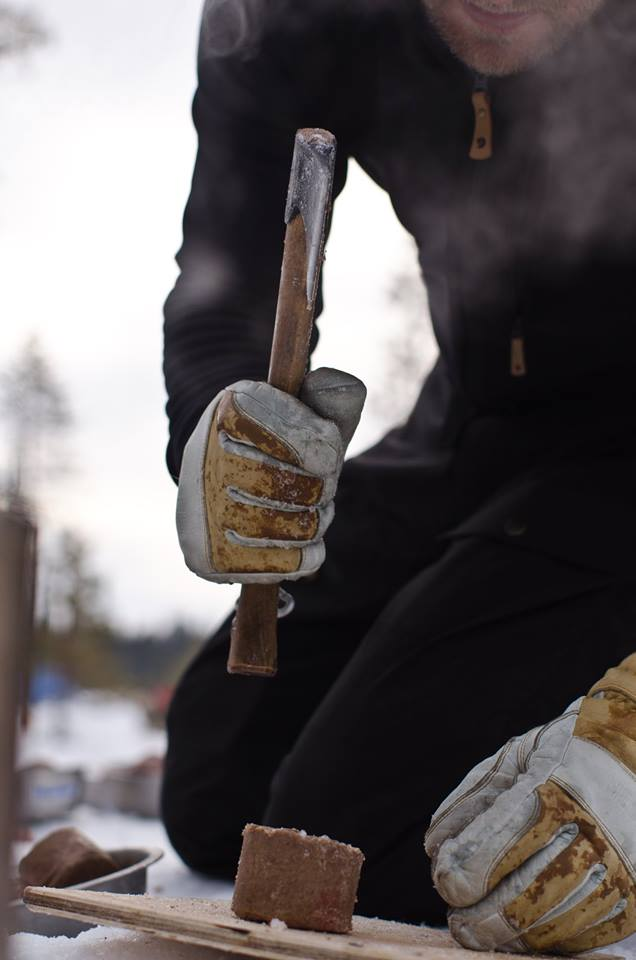 The logs of meat that the dogs eat, consisting mainly of tripe, are frozen solid by the time we arrive at camp. Before they are mixed with boiling water, they must be chopped into pieces with a wood-handled hatchet. (Photo by Søren Hauris Larsen. All rights reserved.)