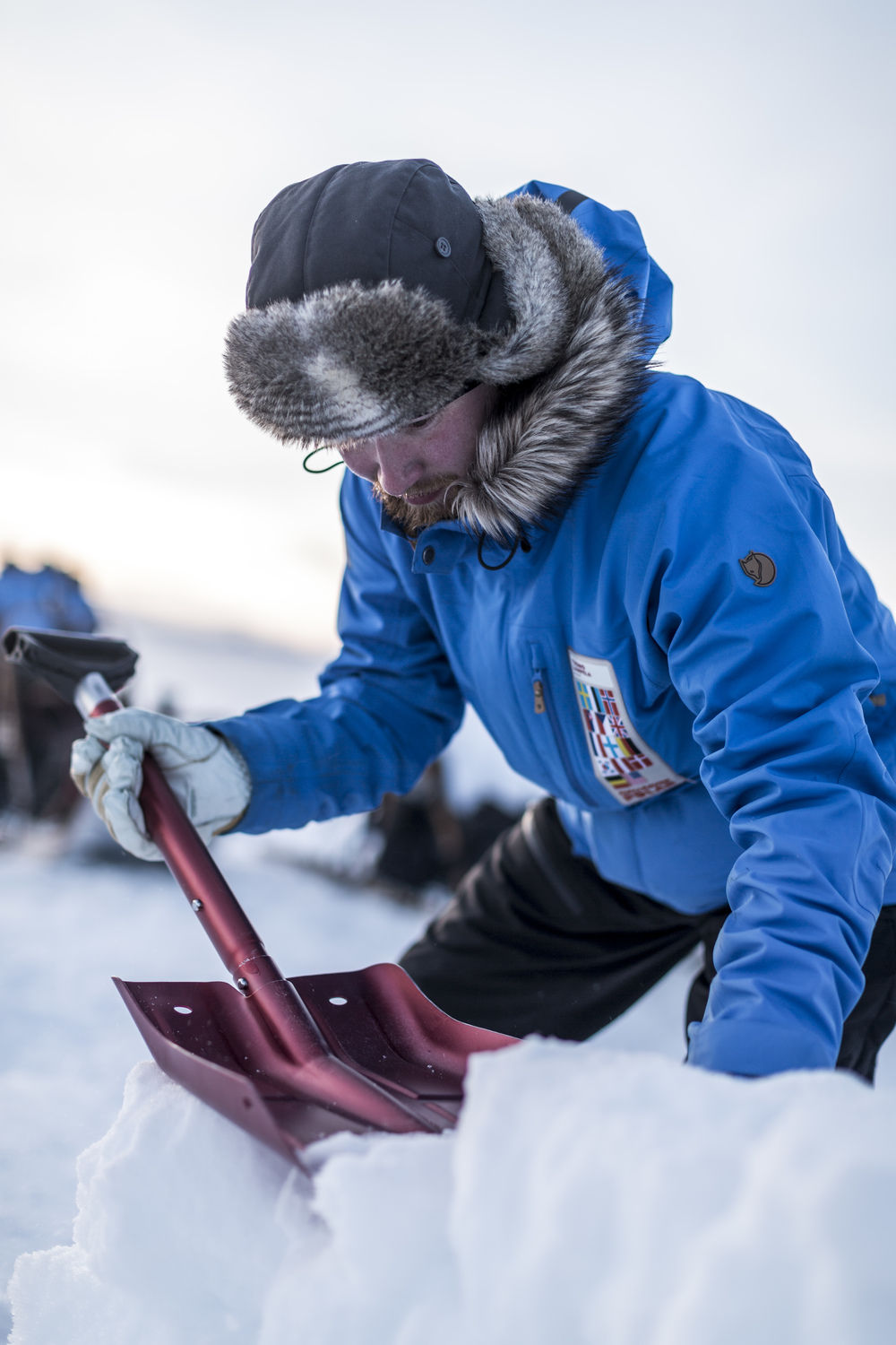 Finnish Fjällräven Polar participant Tuomo Lampela uses his shovel to level and pack a snow block, before adding another layer to his wall. (Photo by Håkan Wike for Fjällräven International. All rights reserved.)