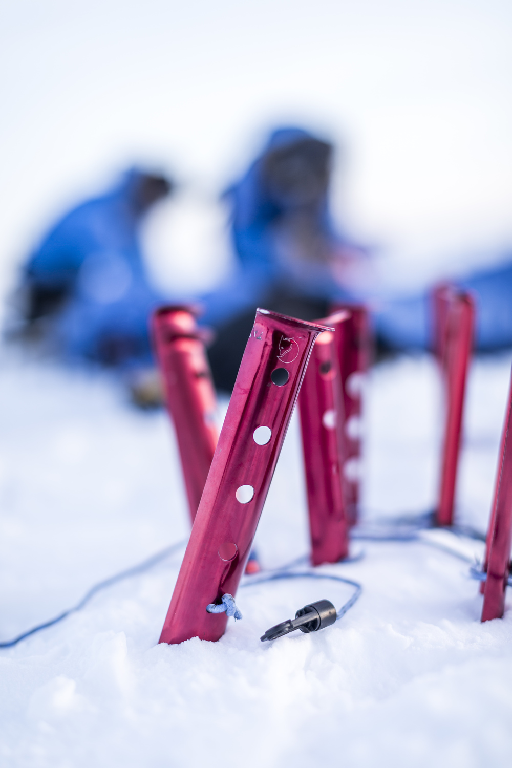 In Råstu's high wind conditions, we use T-anchors to secure the snow pegs. Digging them out of the densely packed snow in the morning, while taking care not to damage the pegs with the aluminum shovel, is a special treat. (Photo by Håkan Wike for Fjällräven International. All rights reserved.)