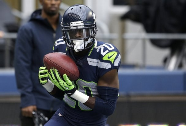 Jeremy Lane looking hot with the ball and holding the baby like a newborn baby.jpg