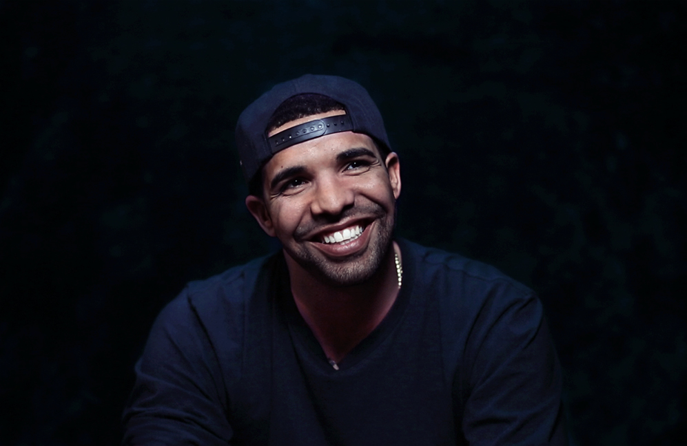 Drake looking really hot and smiling on a black backdrop.jpg