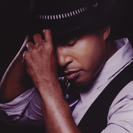 Kevon Edmonds wearing a fedora and pulling it off.jpg