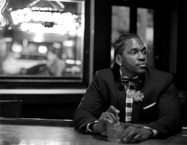Pusha T looking really hot inside a bar with a drink while wearing plaid and a blazer.jpg