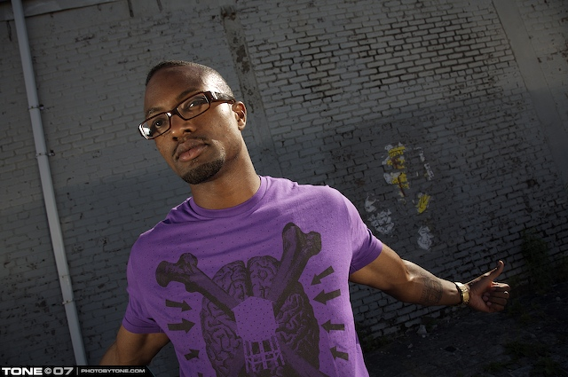 Hezekiah wearing a purple shirt and looking hot against a brick wall.jpg