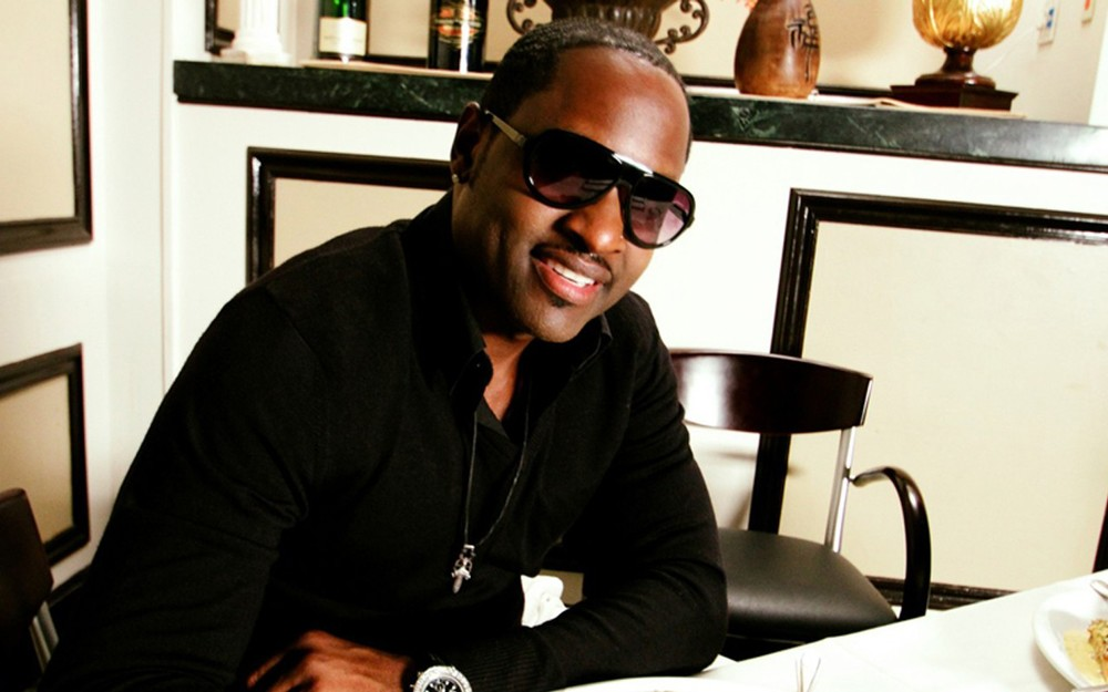 Johnny Gill sitting at home smiling and enjoying life incognito with sunglasses on.jpg