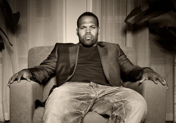 Eric Roberson sitting on a couch looking hot with faded jeans.jpg