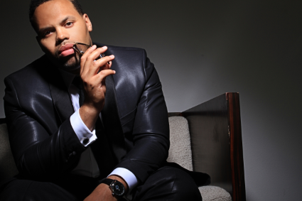 Eric Roberson with his sunglasses up to his mouth.jpg