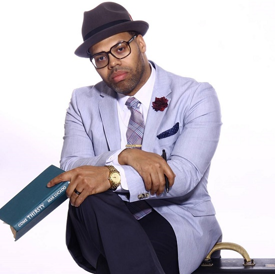Eric Roberson sitting down wearing a lavender blazer looking really hot.jpg