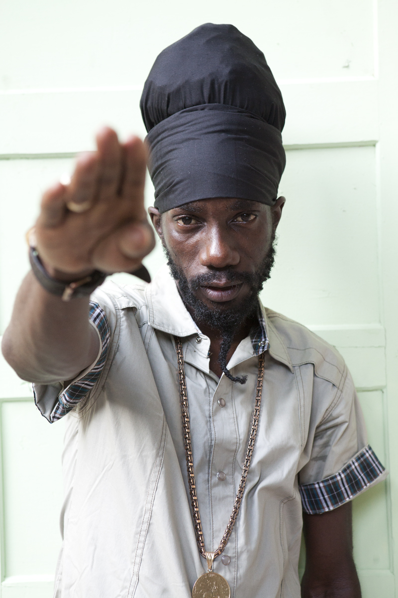 Sizzla looking hot in a white shirt and a medallion around his neck as he stands up and salutes.jpg