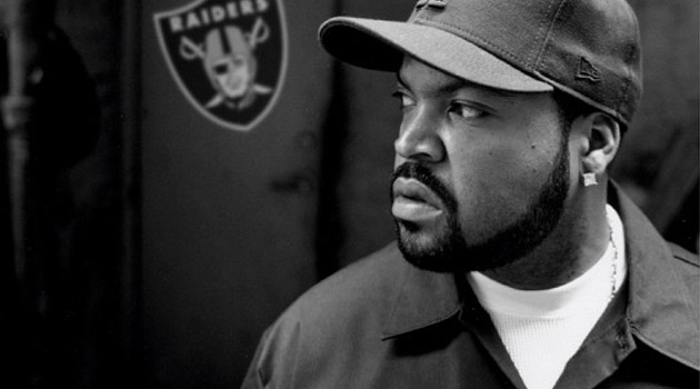 Ice Cube looking hot in a greyscale pic with the Oakland Raiders logo behind him even though the Raiders suck.jpg