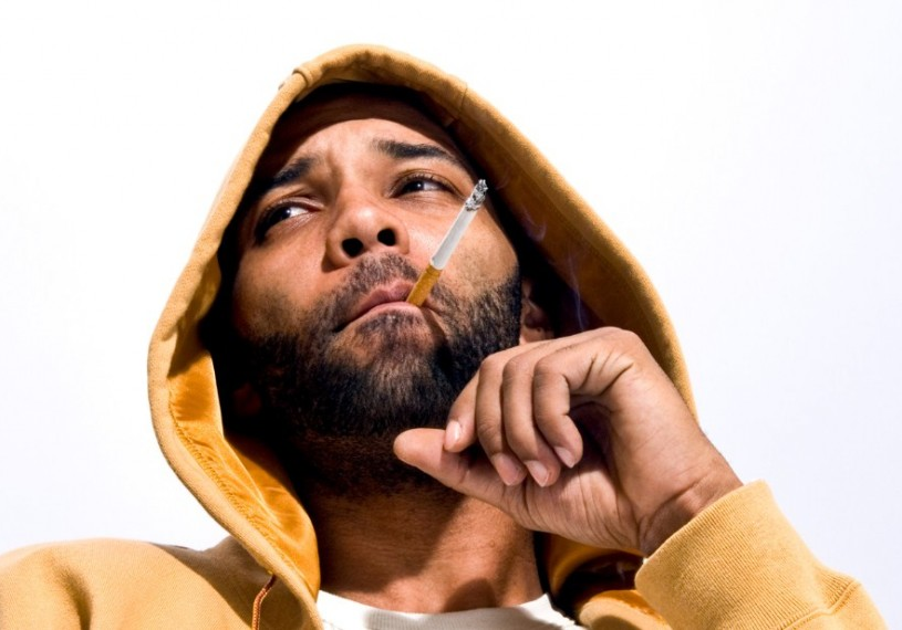 Joe Budden looking hot in a mustard yellow sweatshirt with a hood as he smokes on a cigarette that needs to be ashed asap.jpg