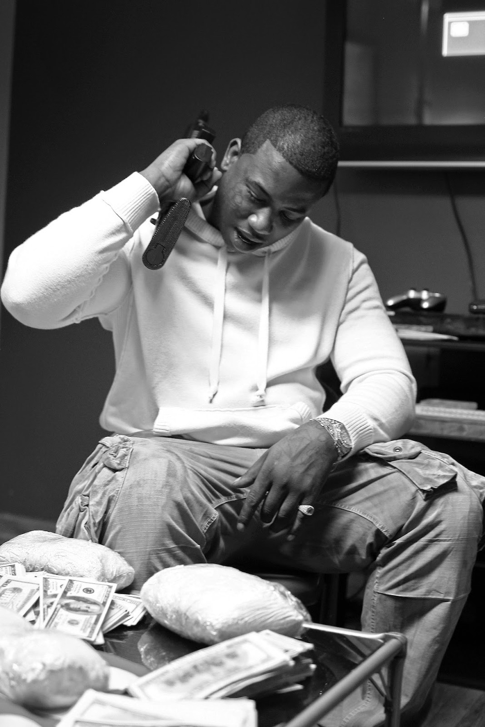 Gucci Mane holding his gun with weed coke and money on the table in front of him.jpg