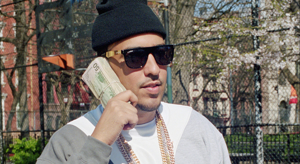 French Montana on the phone with a large sum of money.jpg