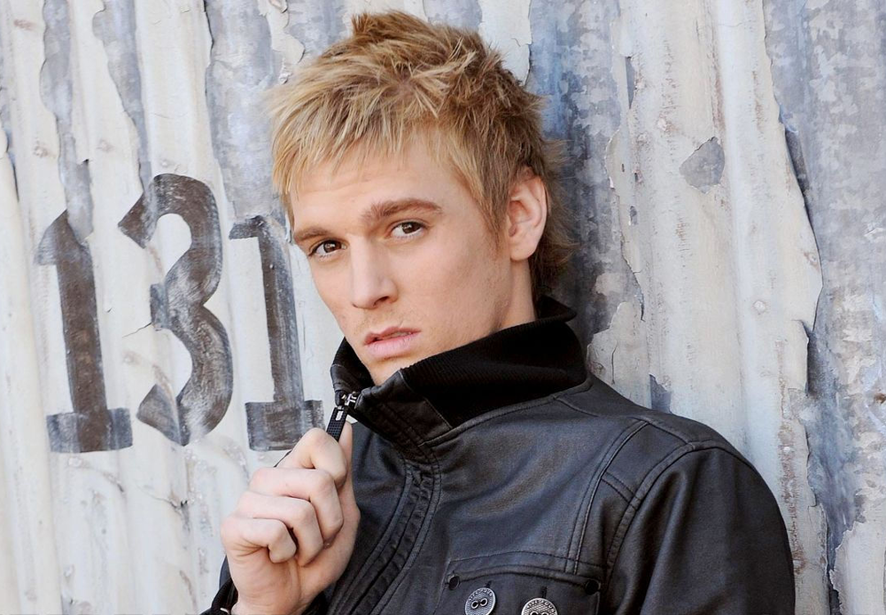 Aaron Carter looking hot against a metal siding in a leather jacket.jpg