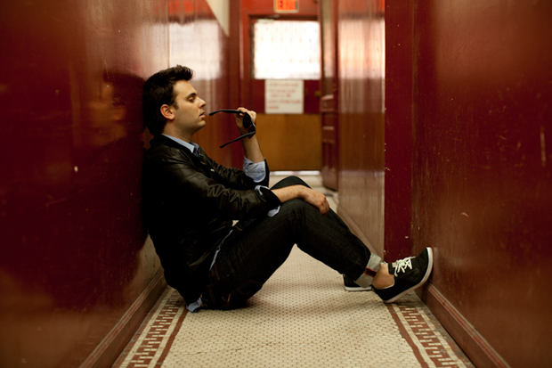 Outasight sitting on the floor in an apartment building's hallway with his sunglasses to his mouth.jpg