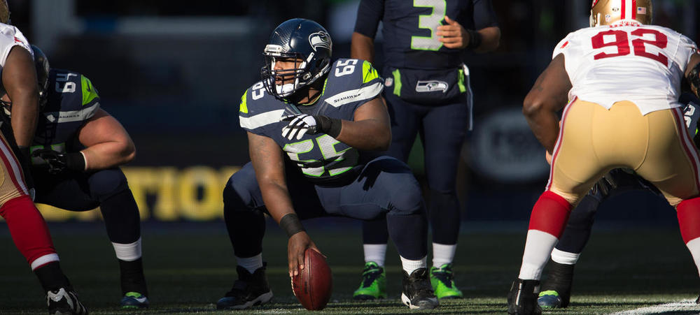 Patrick Lewis squatting down about to throw the football to Russell Wilson as they defeat the 49ers for the 69th time.jpg
