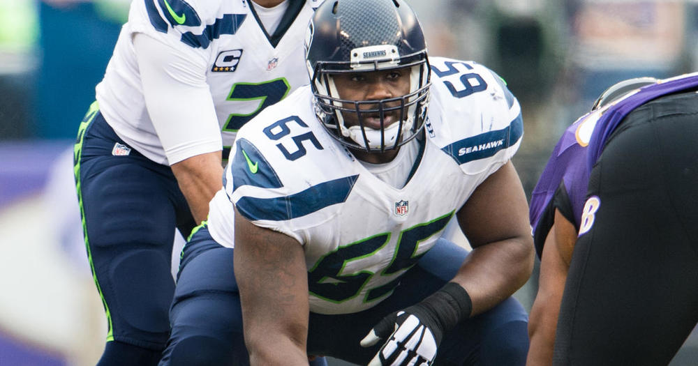 Patrick Lewis looking hot in his white jersey with Russell Wilson behind him looking hot.jpg