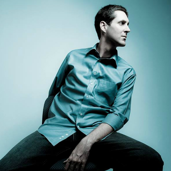 Nicolay sitting on a stool wearing a satin teal shirt that matches the backdrop.jpg