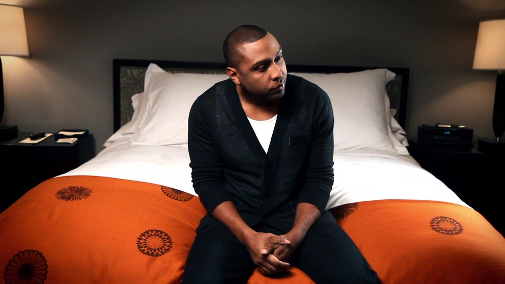 Noel Gourdin sitting on a bed looking hot.jpg