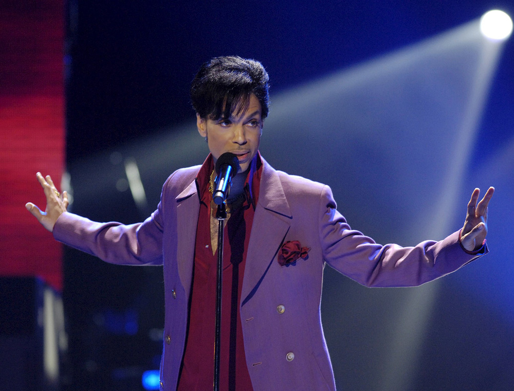 Prince looking hot on stage while talking in a purple suit with his arms up.jpg