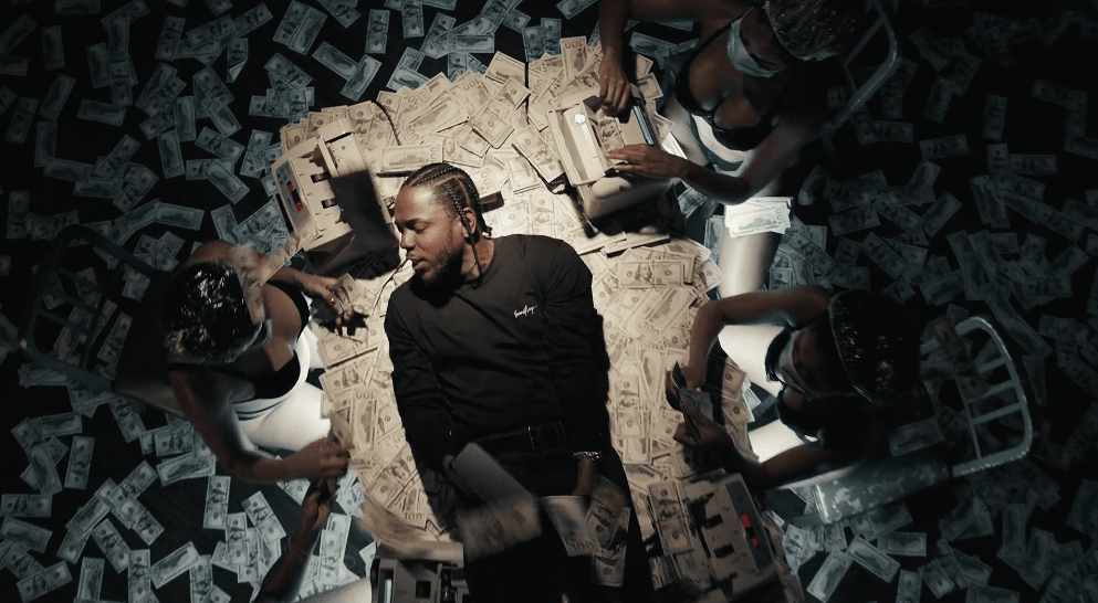 Kendrick Lamar laying on a table while 3 half naked girls make counterfeit money w no gloves on.jpg