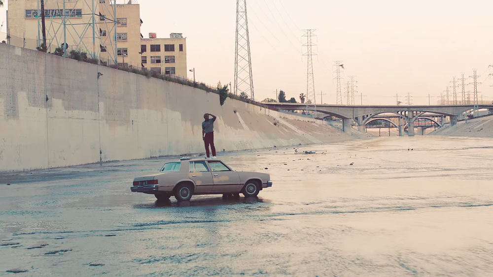 Kendrick Lamar shooting golf balls off the roof of some old ass car in the middle of a dried out ditch or glen.jpg