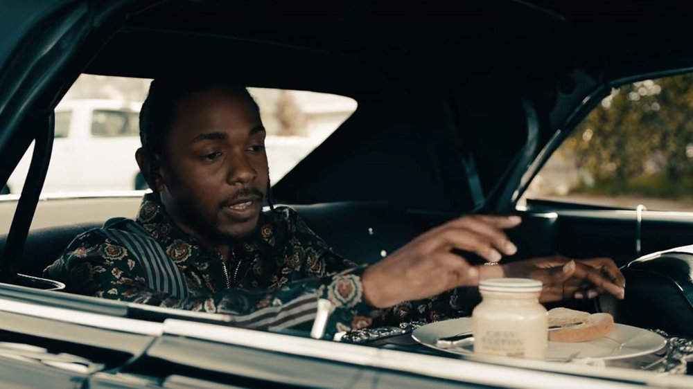 Kendrick Lamar spreading Grey Poupon on a slice of bread in the car.jpg