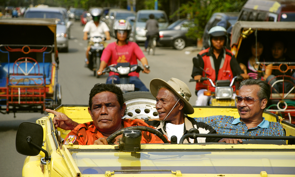 Anwar Congo rides between two of his henchmen through the streets of Jakarta, smiling to friends and supporters.