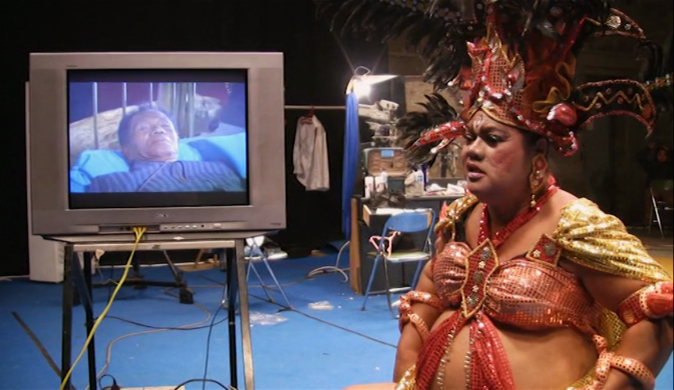 Herman Koto cross-dressing on set as Anwar Congo, on the monitor, prepares for his acting debut.