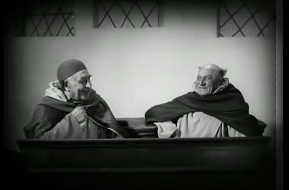 Two priests laughing at the outset of an interrogation that ends in death when Joan of Arc reveals she is unsure of how old she is.