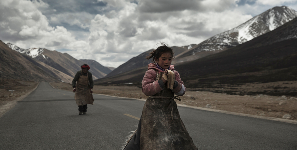 Pilgrims walk a Tibetan highway, prostrating themselves on the pavement at near intervals.