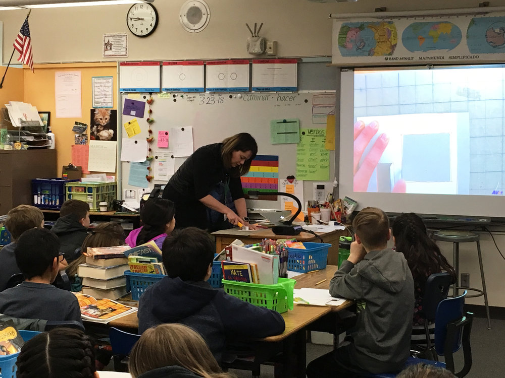 Britni Jessup demonstrates model making techniques to students at the Buena Vista Spanish Immersion School.