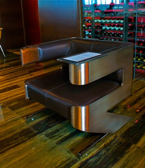 These Tronas chairs are bronze and leather with stainless tray tables.