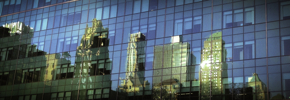 The reflections of Manhattan skyscrapers appear on mirrored windows of a building across from Bryant Park in New York City
