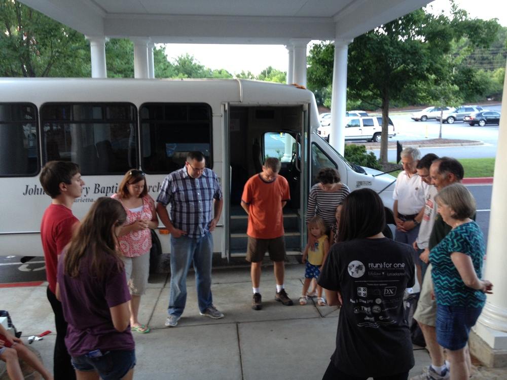 SE Asia team praying with family before leaving