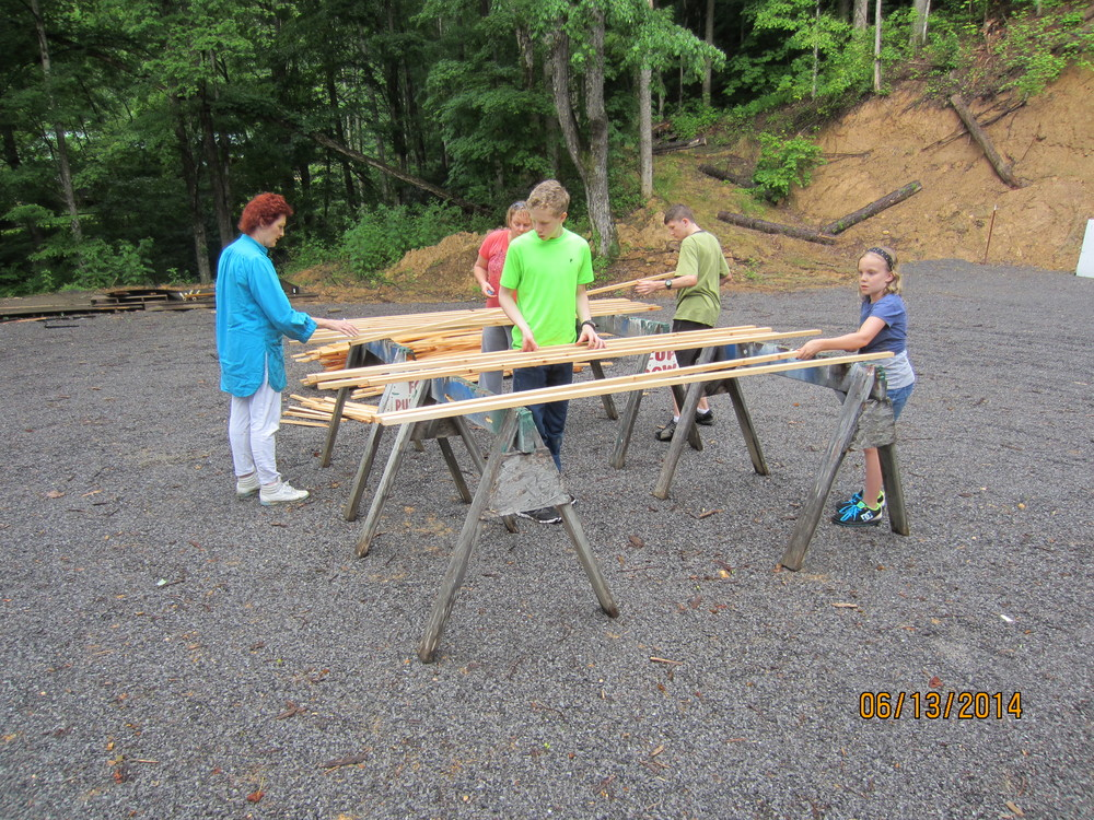 Some of our crew are preparing to paint items for the new shooting range.  Unfortunately, the lumber had gotten so wet, they had to delay finishing this task until tomorrow.  Pictured is Carol Johnson, Heidi, Zach, Oleg and Jorja Reid.