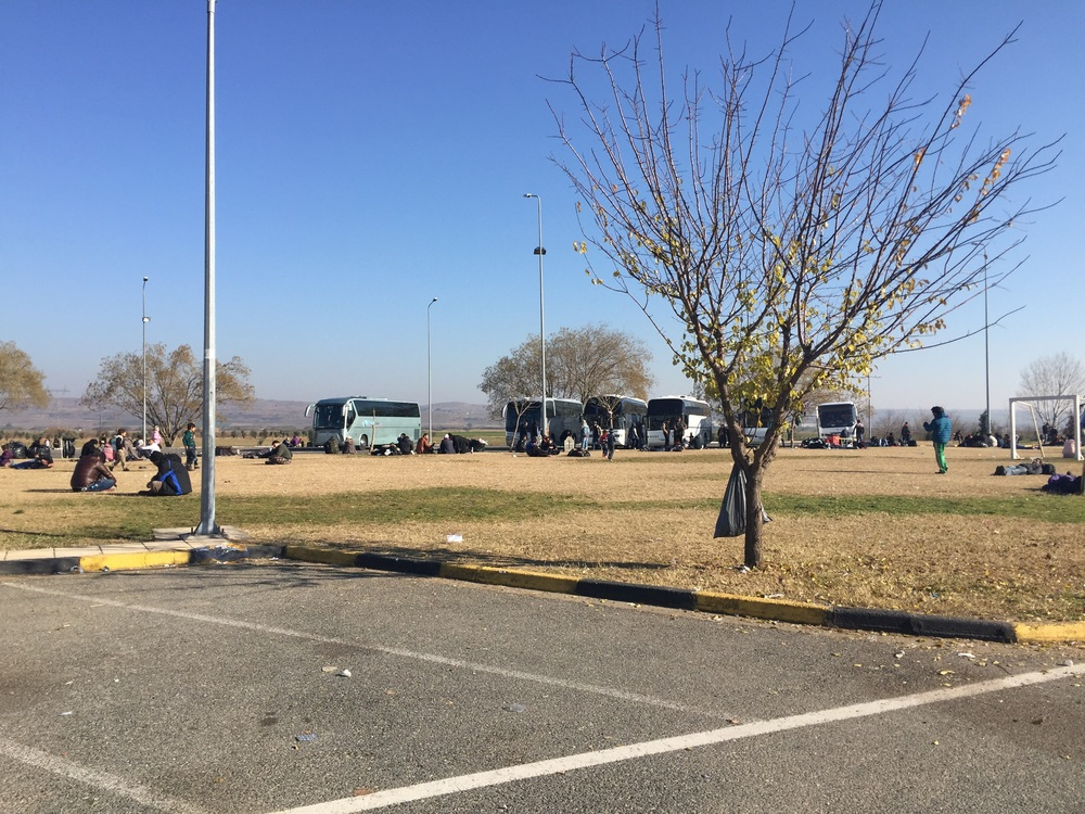 Buses awaiting at the gas station, staging before heading into the camp.