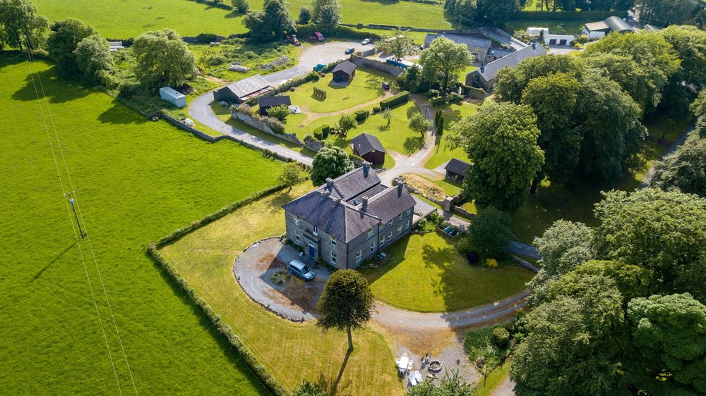 An aerial view of Lacken House and the surrounding grounds and chalets.