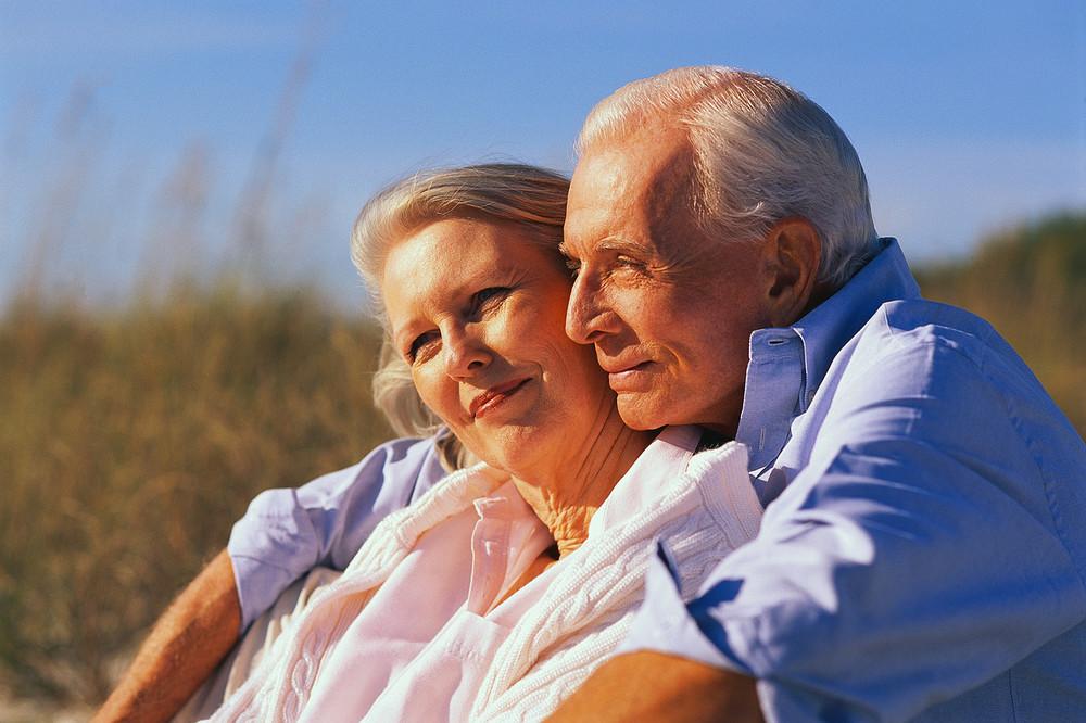 Senior couple sitting on beach