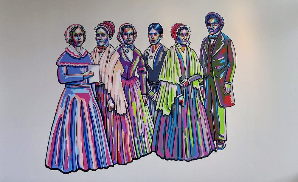 Left to Right: Elizabeth Cady Stanton and Lucretia Mott (the originators of the 1848 Seneca Falls Women's Rights Convention), Martha Coffin Wright, Jane Hunt, and Mary Ann M'Clintock (Convention organizers) , and Frederick Douglass (notable Convention attendee and champion for women's rights).
