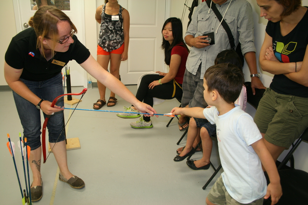 OFAH staff talk to New Canadians Centre visitors about the different  parts of an arrow during instruction on the Excalibur Archery Range.