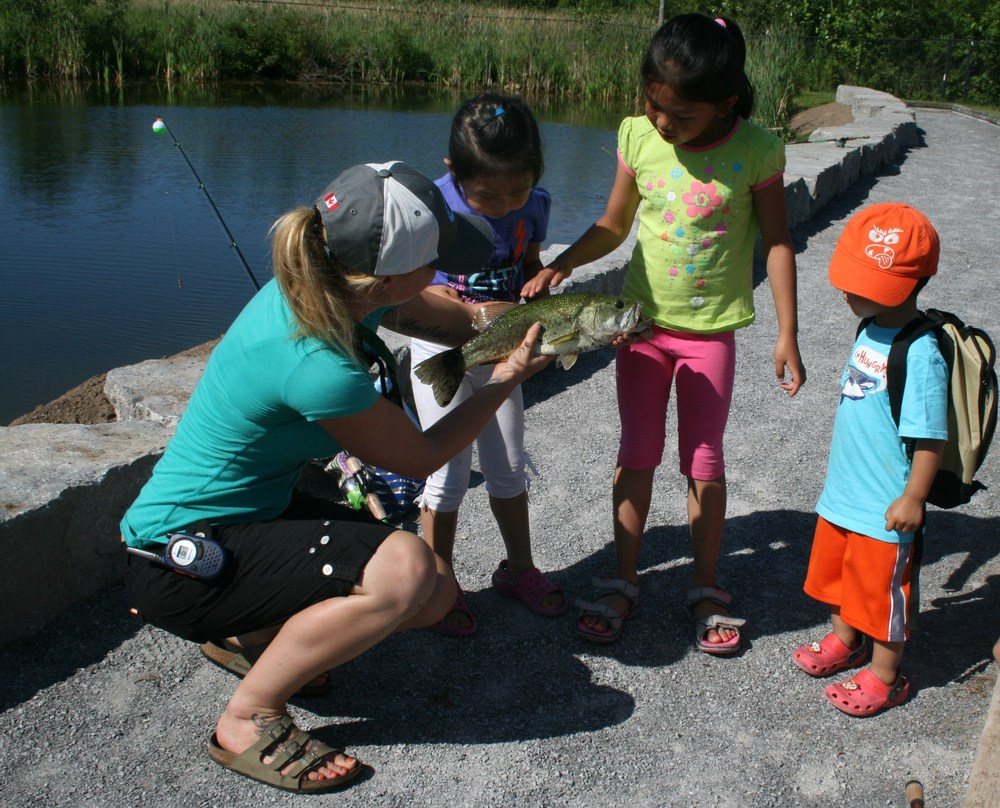 An OFAH staff member teaches a group of children about their catch before releasing it back into the pond.