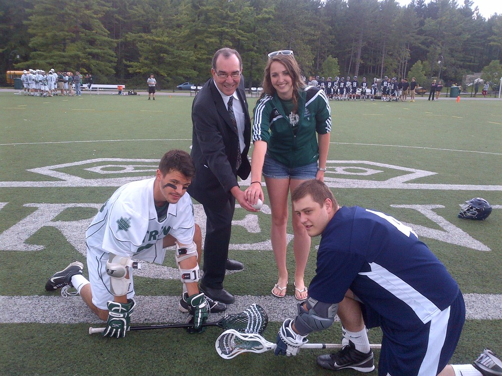 Ceremonial faceoff: Trent president Dr. Steven E. Franklin with Rettie and lacrosse players Brock McGillis (left) from Trent and Brodie Birkhoff (right) from Nipissing (Brodie is a Peterborough native)
