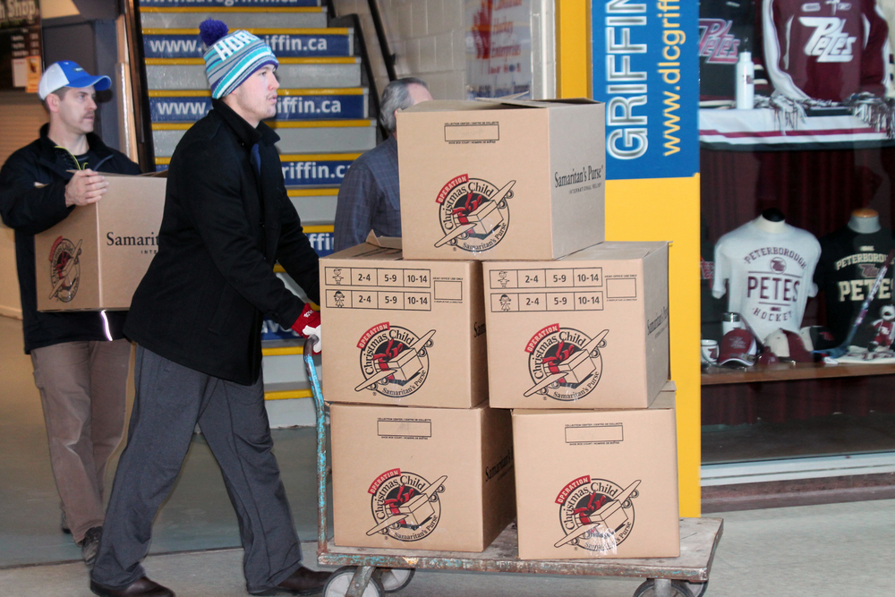 Petes player Nick Ritchie helping load shoeboxes