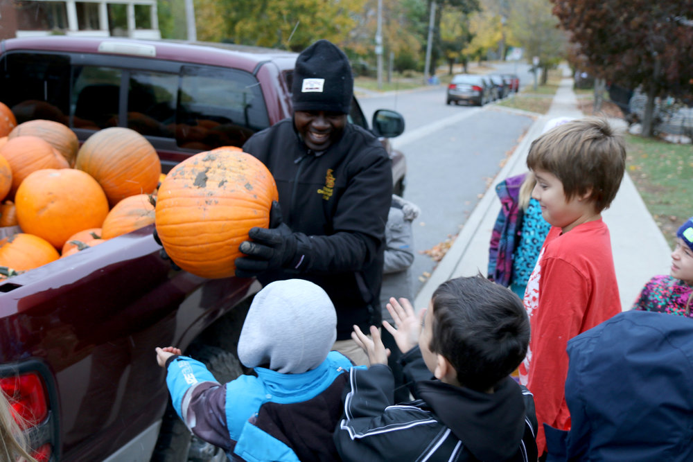 Louis distributes pumpkins to happy students at Immaculate Conception