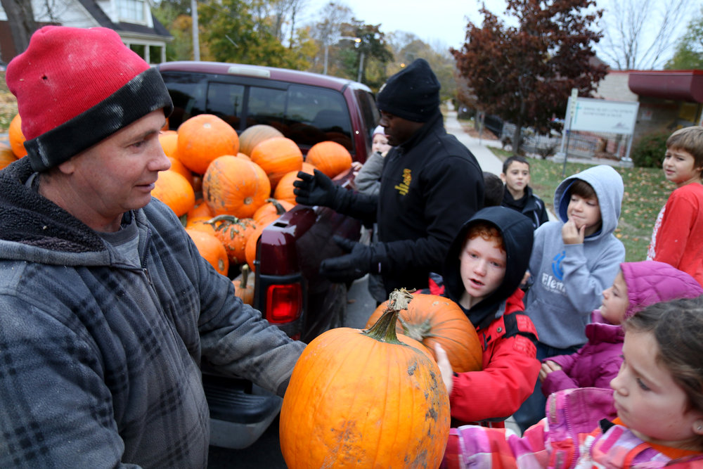Peter Leahy and Louis giving out pumpkins to the kids