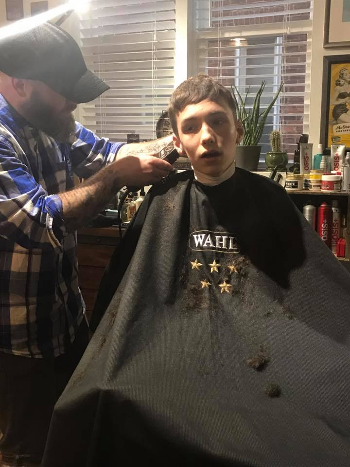 Stylist Adam Murray begins cutting Aidan's hair