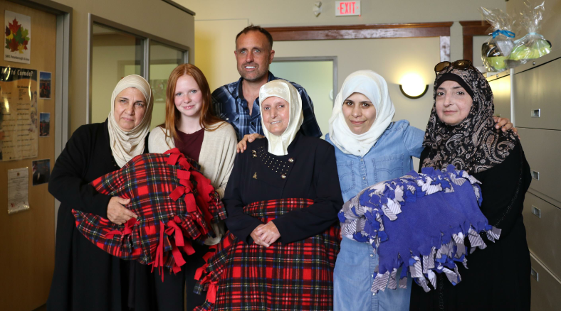 Left to right:  Hend Altech, United Way Youth Ambassador Faith Dickinson, United Way Chair Neil Morton, Malaka Tonbakj, Abir Al Hattab and Sabah Alhamwi  Extending warmth and comfort to newcomer women from Syria, Cuddles for Cancer and United Way Youth Ambassador Faith Dickinson demonstrates the power of community